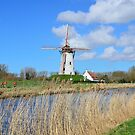Bikers passing by an old windmill in Damme, Flanders by 7horses