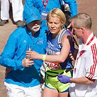 A runner is helped after crossing the finish line of the London Marathon by Keith Larby