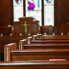 Church Pews with Stained Glass Beyond Pulpit by dbvirago