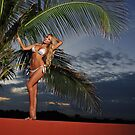 Model  poses at sunset with palm tree on background  by Anton Oparin