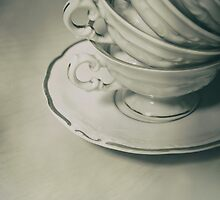 Four teacups and the small plate on the table by JBlaminsky