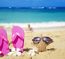 Flip flops and starfish with sunglasses on sandy beach by ellensmile