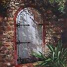 Decorative door in archway set in stone wall surrounded by plants by martyee