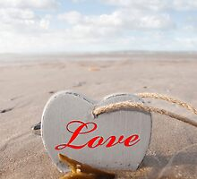 inscribed wooden love heart in the sand by morrbyte