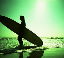 Surfer carrying surfboard in surreal silhouette in green in sea ocean water by beach 35mm analog xpro cross lomo lca photo by edwardolive