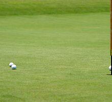 Golf balls near flagstick by Henrik Lehnerer