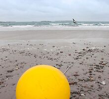 giant yellow buoy on beach by morrbyte