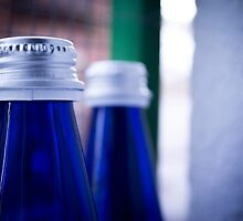 Gray stopper bottle of sparkling water blue glass by GemaIbarra