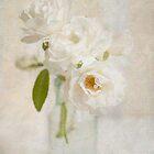 Roses in an antique bottle by Jill Ferry