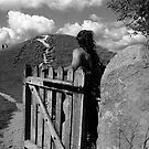 YOUNG WOMAN CLOSES WOODEN GATE by kfbphoto