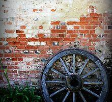 Old Cart Wheel against Brick Wall by fantasytripp