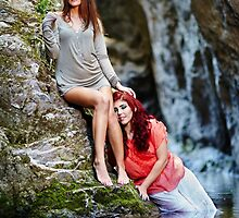 Two beautiful young women leaning on rocks beside a river by naturalis