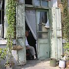 Man in doorway - Dalian China 2002 by Roger Smith