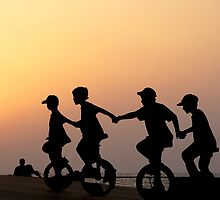 Children on one wheel bicycle by Moshe Cohen