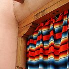 Mexican blanket hanging in adobe in Taos, NM by Ronee van Deemter