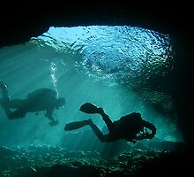 Divers exiting a cave by Agnes Milowka
