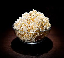 crunchy popcorn in glass bowl by Arletta Cwalina