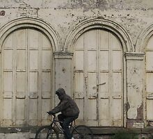Cycling past a building of years gone by. by scenebyawoman