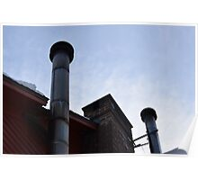 two metal smoke stacks under a blue sky Poster