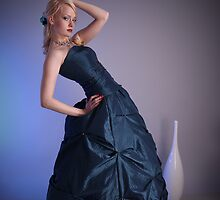 Beautiful young woman wearing a blue prom dress by Sandra Kemppainen