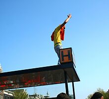 Dutch man celebrating Queens Day on top of a tram shelter by Mishimoto