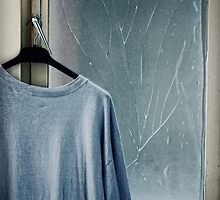 Hanging T-shirt and broken window pane by Silvia Ganora