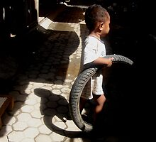 Boy and tire by Carlito da Costa by Friends  of Suai