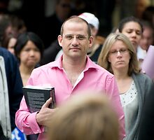Man in pink shirt with book by Chris Curnow
