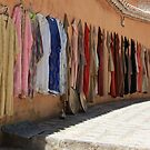 Djellabas hanging on Chefchaouen wall by Christine Oakley