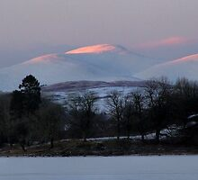 Sunset reflected on the snowy hills by Kim  Ayres