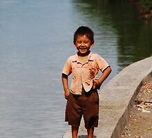 Smiling Balinese boy down by the river by Michael Brewer