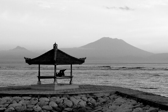 Lone figure in beachside pagoda, sacred mountain Gunung Agung in background. Bali, Indonesia by Sheldon Levis