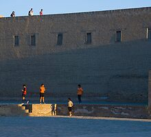 Uzbek boys at Khiva old city walls at dusk by Speedy