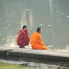 Two monks having a quite minute at sunset at Angkor Wat Cambodia by Adrienne Bartl