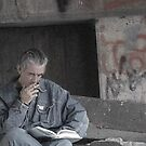 Homeless man reading by Amanda Huggins
