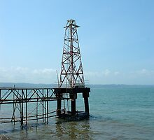 lighthouse on beach by bayu harsa