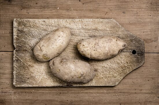 Potatoes on wooden table. by Pablo Caridad