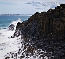 Waves break onto Fingal Head by John Quixley