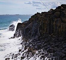 Waves break onto Fingal Head by John Quixley