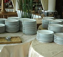 stack of white plates by bayu harsa