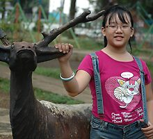little girl stand up beside deer statue by bayu harsa