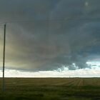stormy clouds over prairie field by Matte Downey