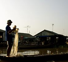 Vietnam - Man tending to his fishing nets on the Mekong Delta by Chris Bishop