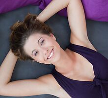 Girl lying on the bed with big smile by Vlada Jerkovic