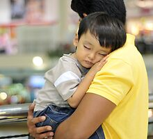 Sleeping child in hug on shoulder by Mohd Fadzli Abu Bakar