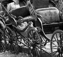 A Calcutta rickshaw wallah relaxes in the sun by steve nicholson
